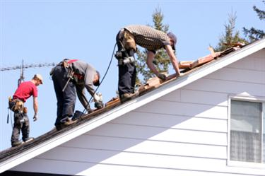 Roof Installation in Throggs Neck NY. Three roofers laying new shingle on a roof in Throggs Neck.